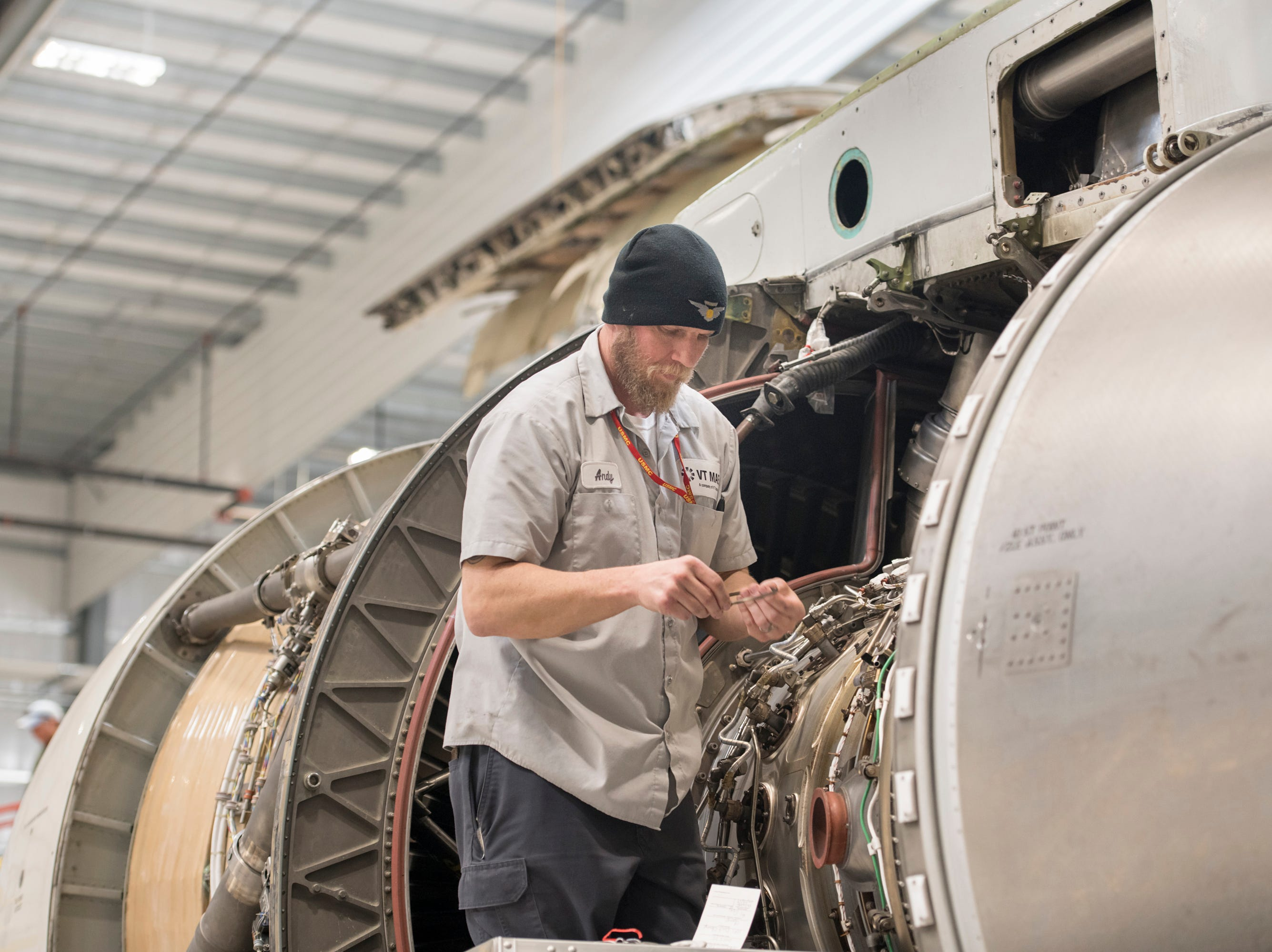 Mechanic Andy Bauer works on a jet engine at ST Engineering at the Pensacola International Airport in Pensacola on Friday, February 8, 2019.