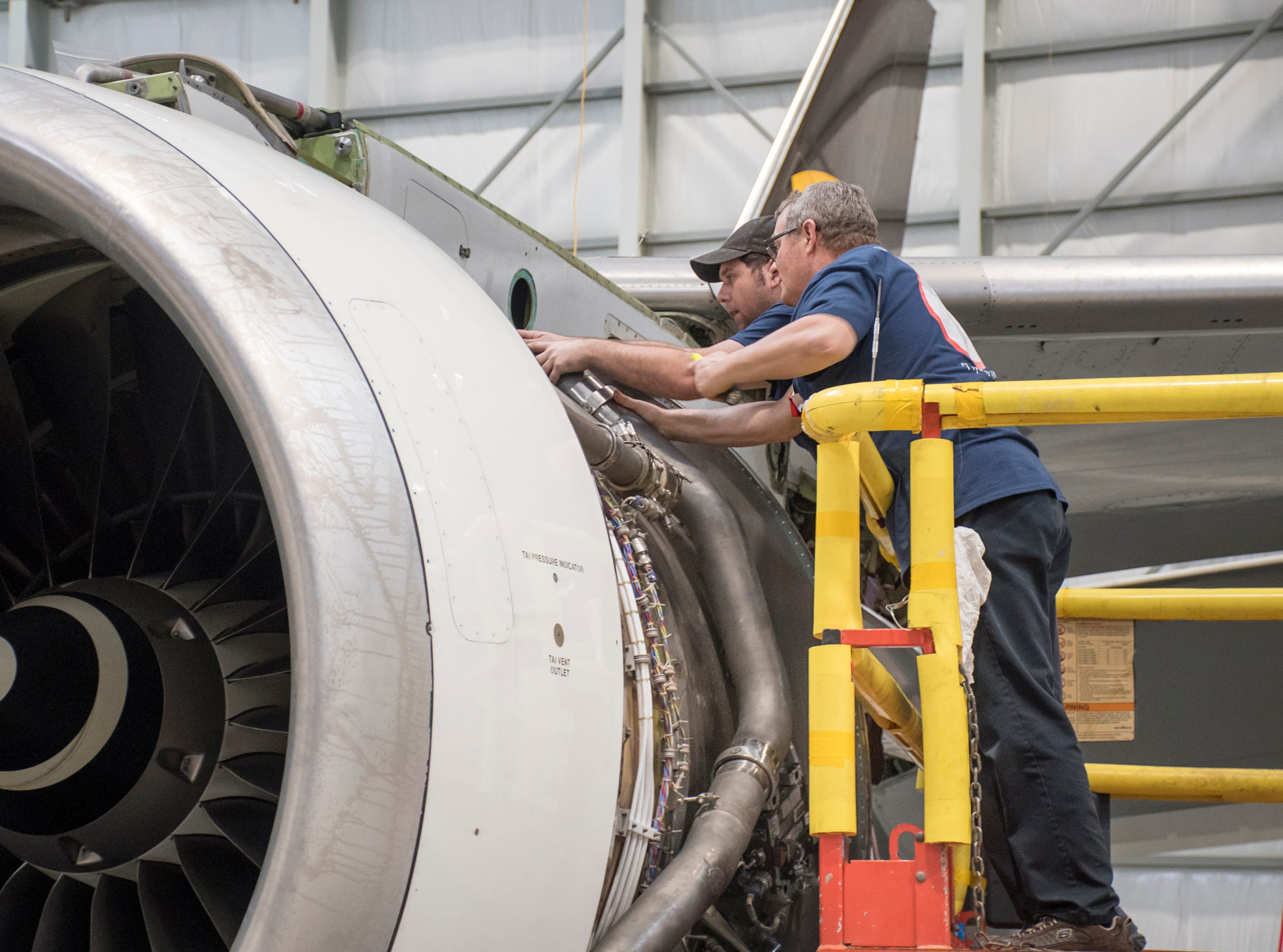 Mechanics Eric Matherly, right, and Justin Wilson work on a jet engine in the hangar at ST Engineering at the Pensacola International Airport in Pensacola on Friday, February 8, 2019.