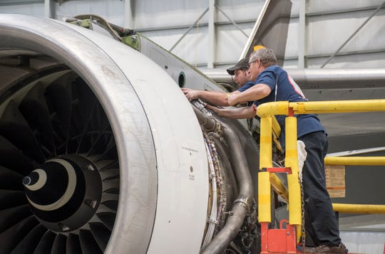 Mechanics Eric Matherly, right, and Justin Wilson work Friday on a jet engine in the hangar at ST Engineering at the Pensacola International Airport. The Triumph Gulf Coast board has approved granting an additional $10 million, on top of the previously granted $66 million, for a project to expand the company's aircraft maintenance, repair and overhaul facility at the airport.