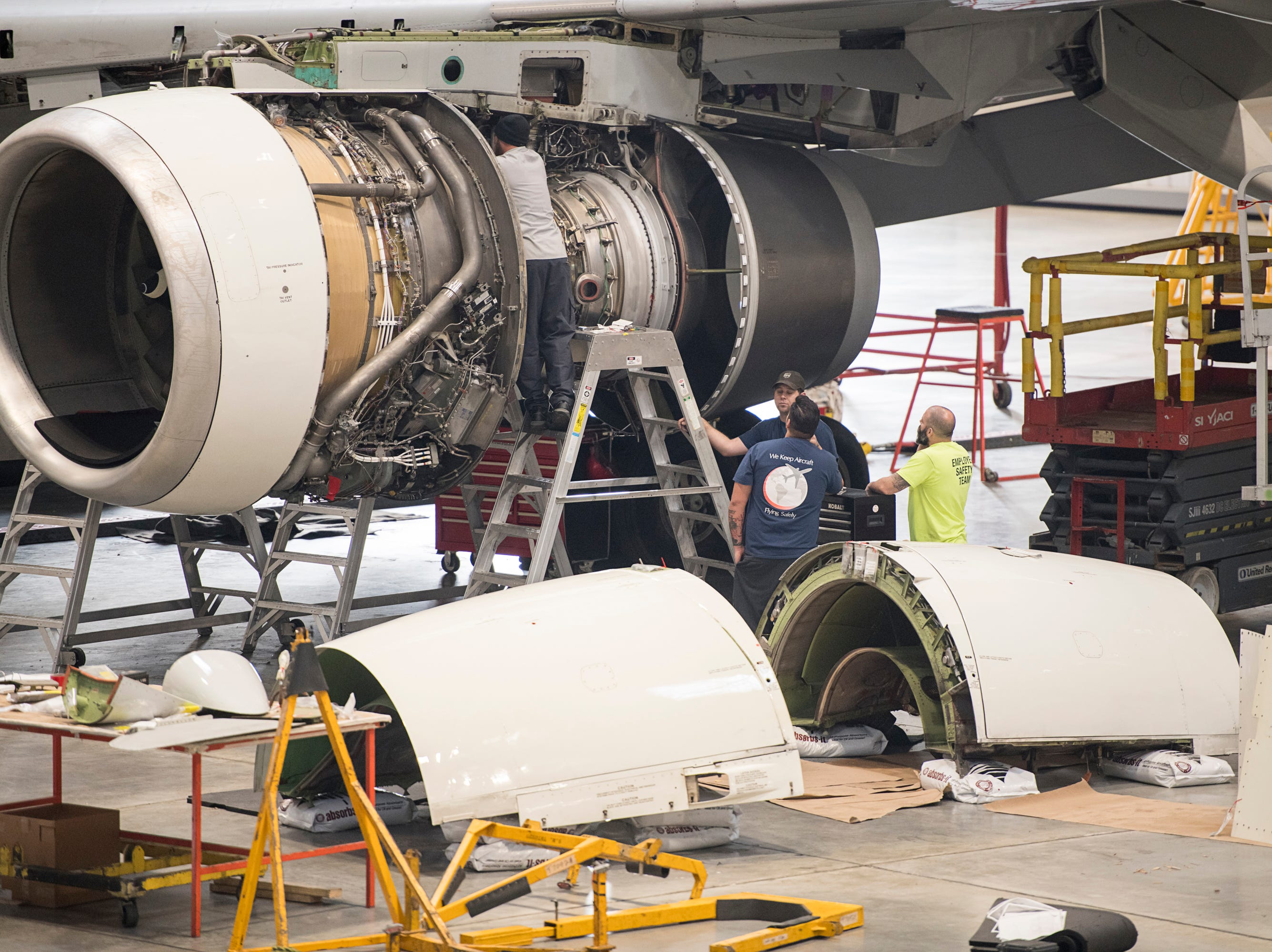 Mechanic Andy Bauer, top, works on a jet engine at ST Engineering at the Pensacola International Airport in Pensacola on Friday, February 8, 2019.