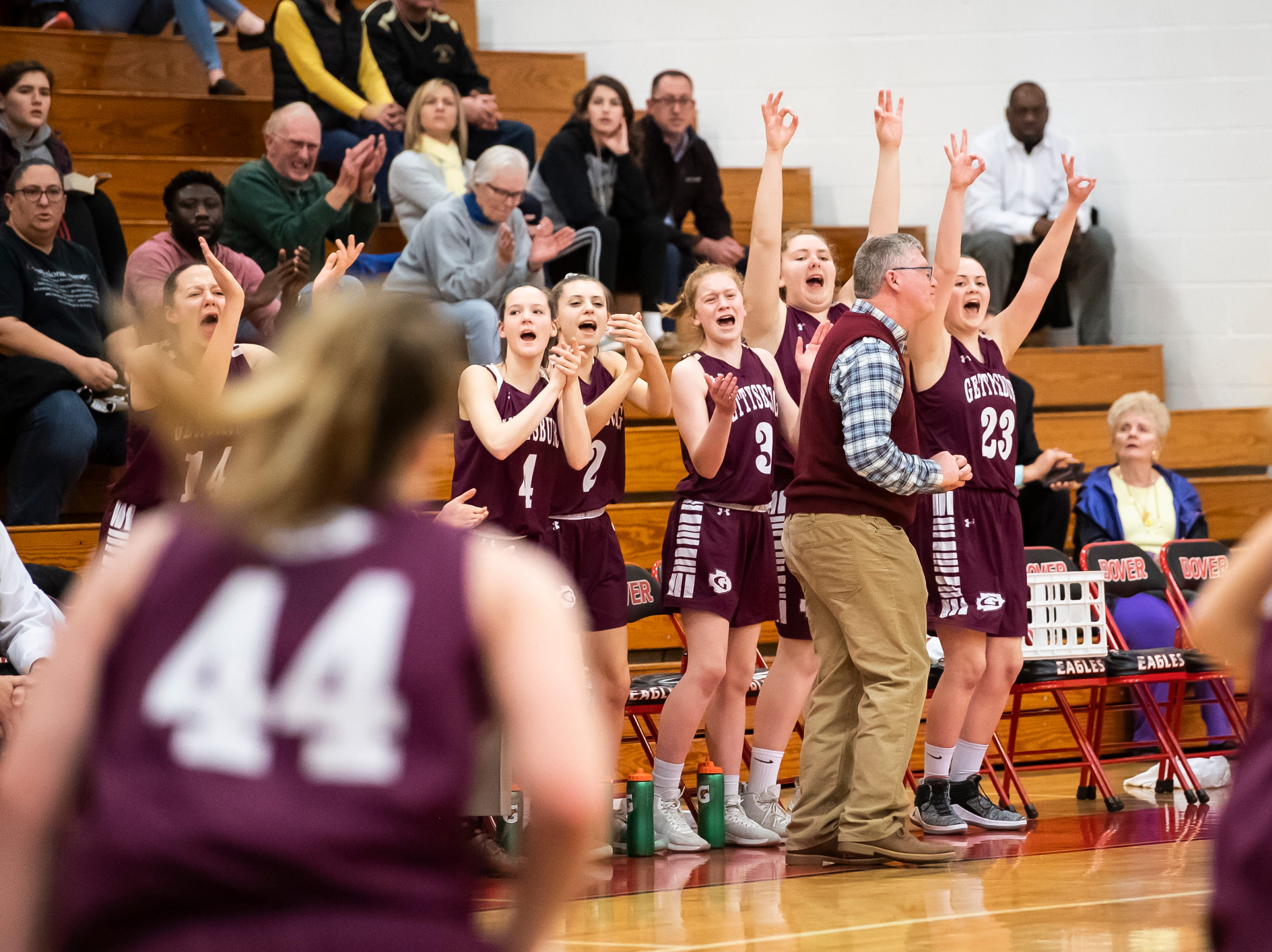 The Gettysburg bench reacts after Cheyenne Proctor scores on a 3-pointer during play against Delone Catholic in a YAIAA quarterfinal game at Dover High School Friday, February 8, 2019.