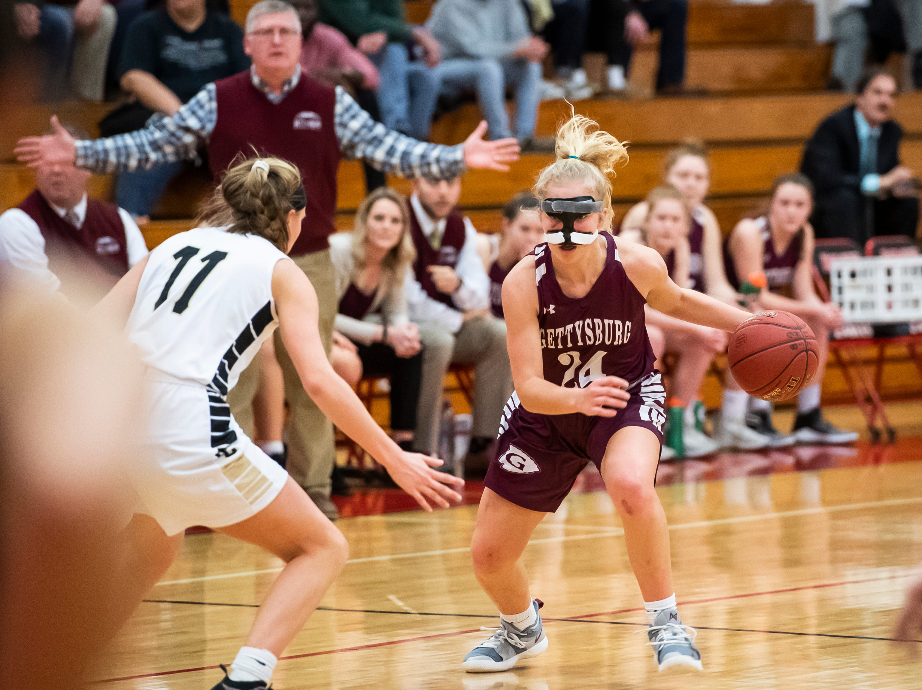 """Gettysburg's Anne Bair dribbles down the court during play against Delone Catholic in a YAIAA quarterfinal game at Dover High School Friday, February 8, 2019. """"It's not badly broken,"""" Jeff Bair said of Anne Bair's broken nose, which happened during a game against Kennard-Dale Saturday. """"Doctor's saw it. She wears the mask, she's fine...she plays with a lot of courage, and she wanted to really play at a high level."""""""