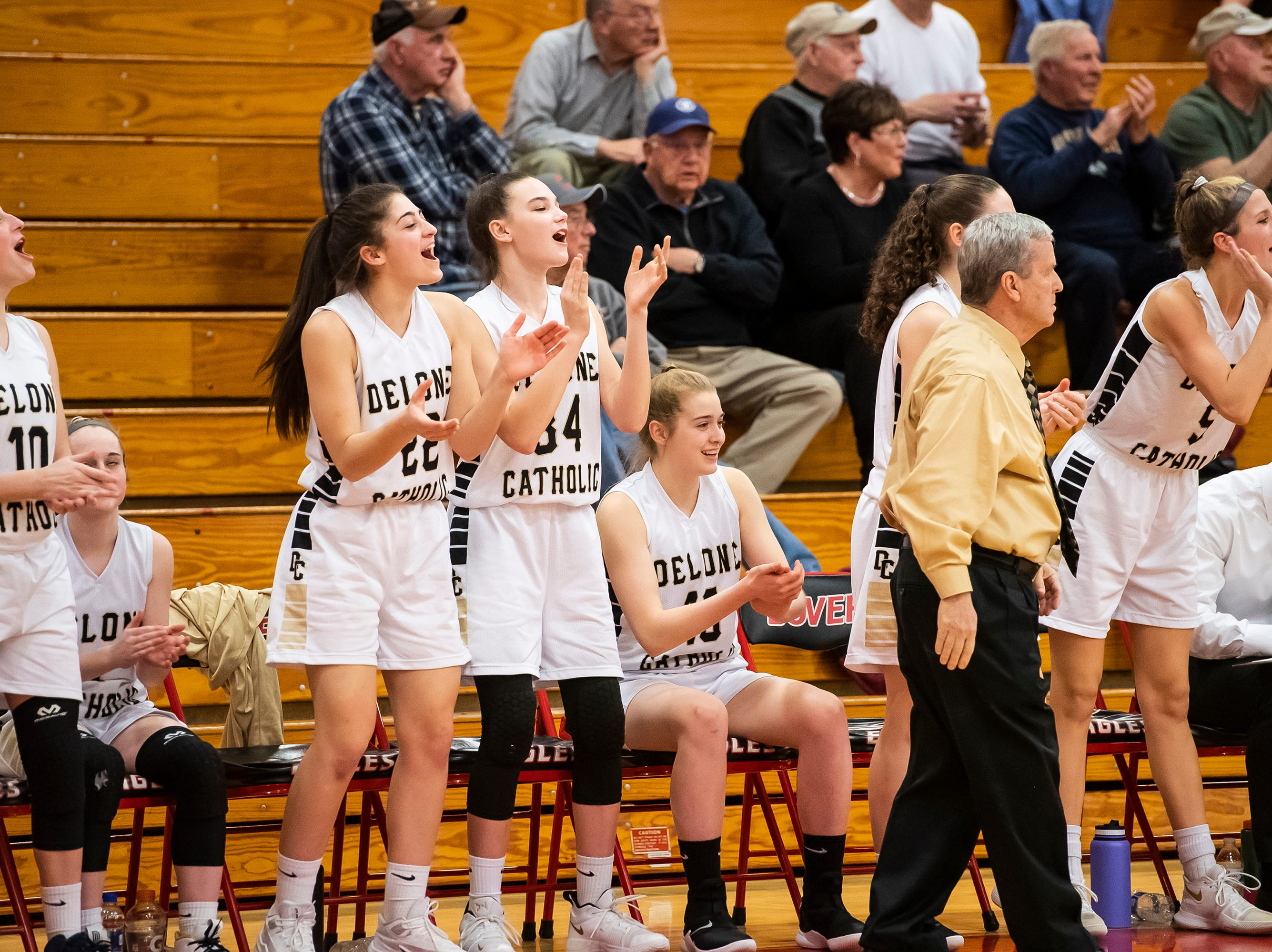 The Delone Catholic bench reacts after the Squirettes score on a 3-pointer during play against Gettysburg in a YAIAA quarterfinal game at Dover High School Friday, February 8, 2019.