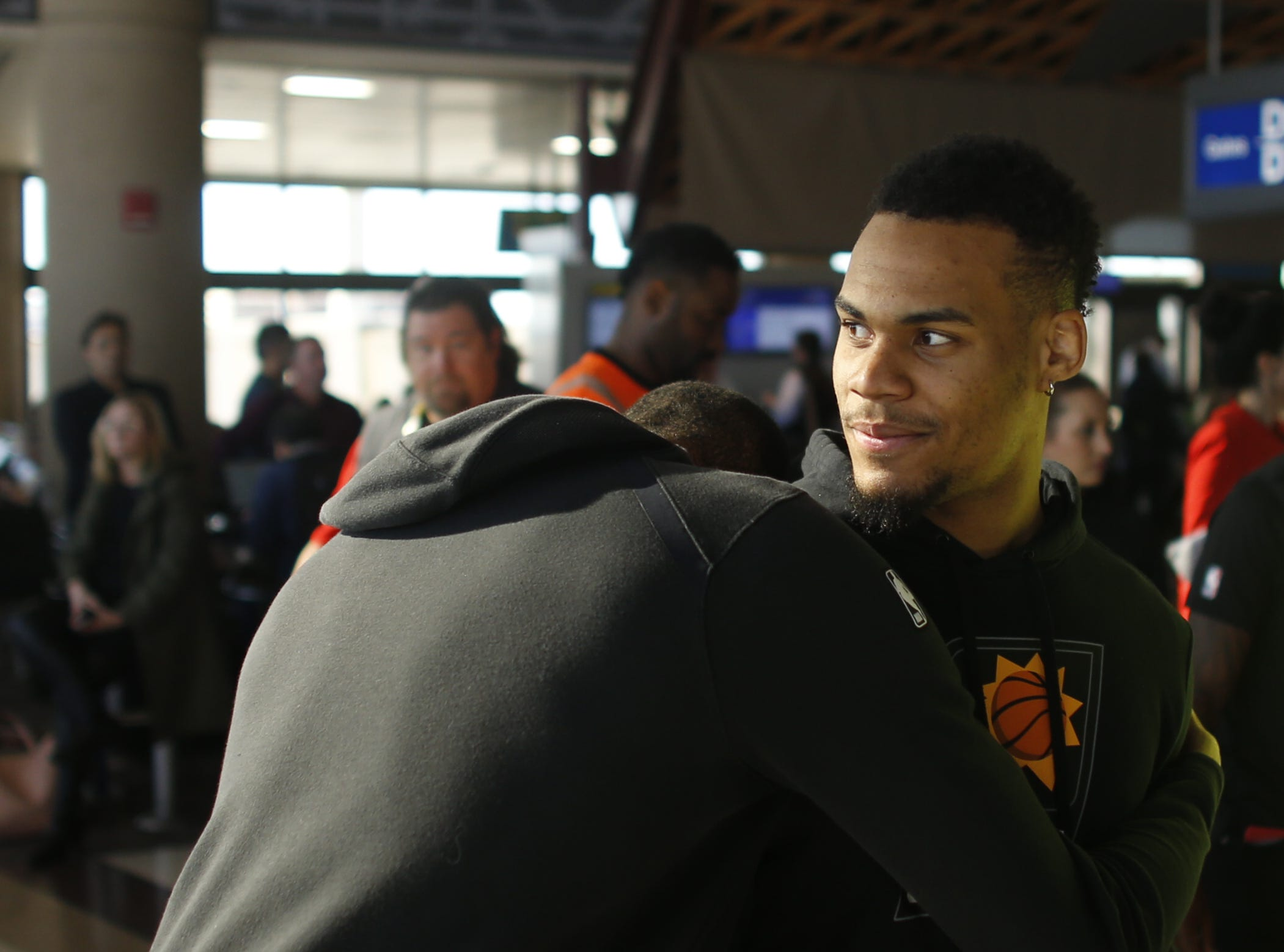 "Suns' Mikal Bridges hugs onto teammate Elie Okobo laughing during a Suns and Southwest ""trading places"" event where players took on the roles of Southwest Airlines employees at Phoenix Sky Harbor Airport in Phoenix, Ariz. on February 7, 2019."