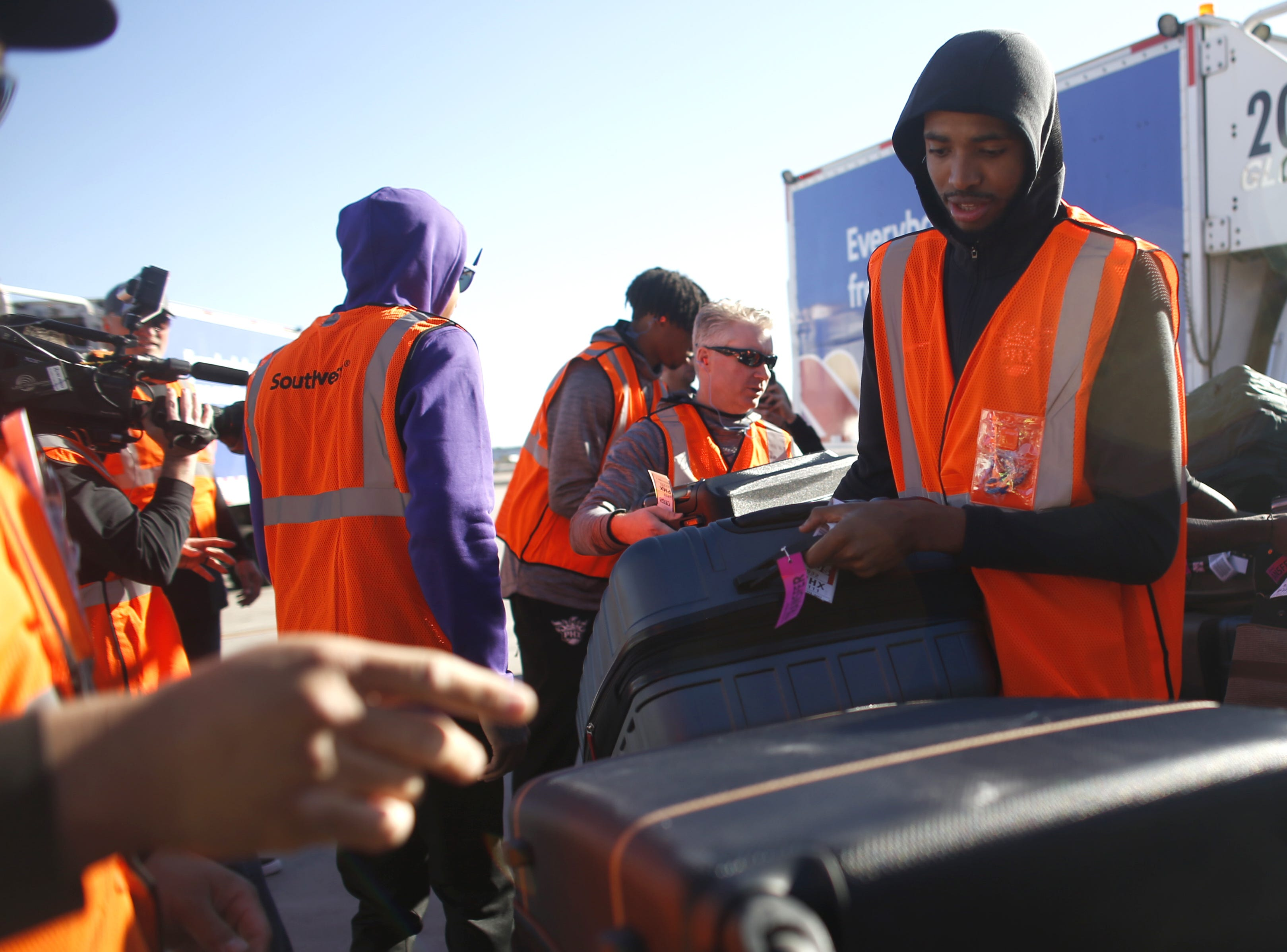 "Suns' Mikal Bridges places a bag on the conveyor belt during a Suns and Southwest ""trading places"" event where players took on the roles of Southwest Airlines employees at Phoenix Sky Harbor Airport in Phoenix, Ariz. on February 7, 2019."