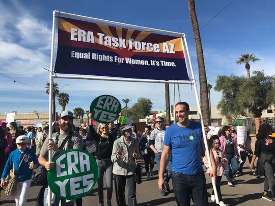 Nik Rasheta (left, in hat), whose wife, Annisa Rasheta, heads Mormons for ERA in Arizona, carries a banner at the Women's March in Phoenix.