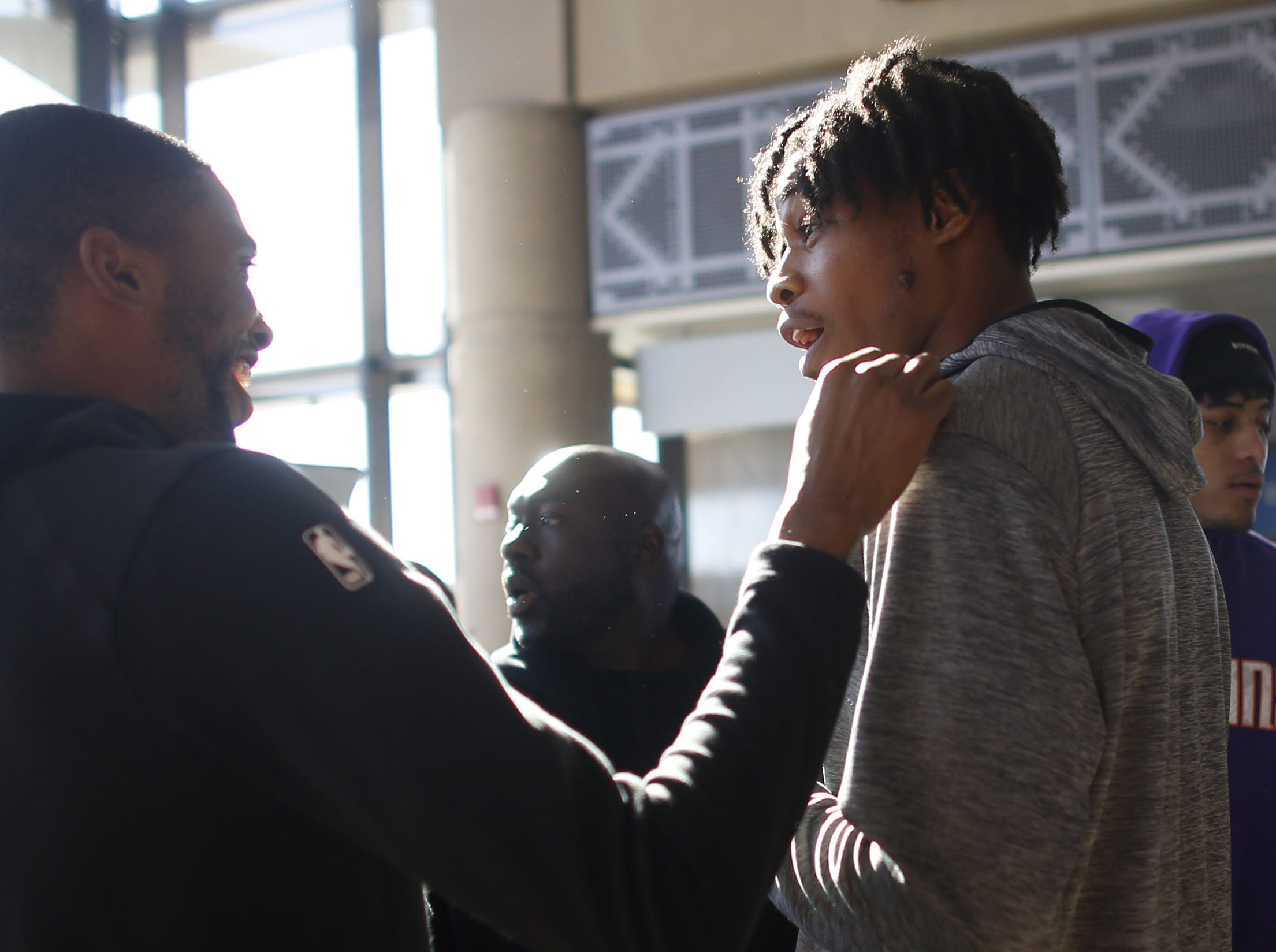 "Suns' Mikal Bridges (L) jokes with Richaun Holmes before they greet fans and airline passengers during a Suns and Southwest ""trading places"" event where players took on the roles of Southwest Airlines employees at Phoenix Sky Harbor Airport in Phoenix, Ariz. on February 7, 2019."