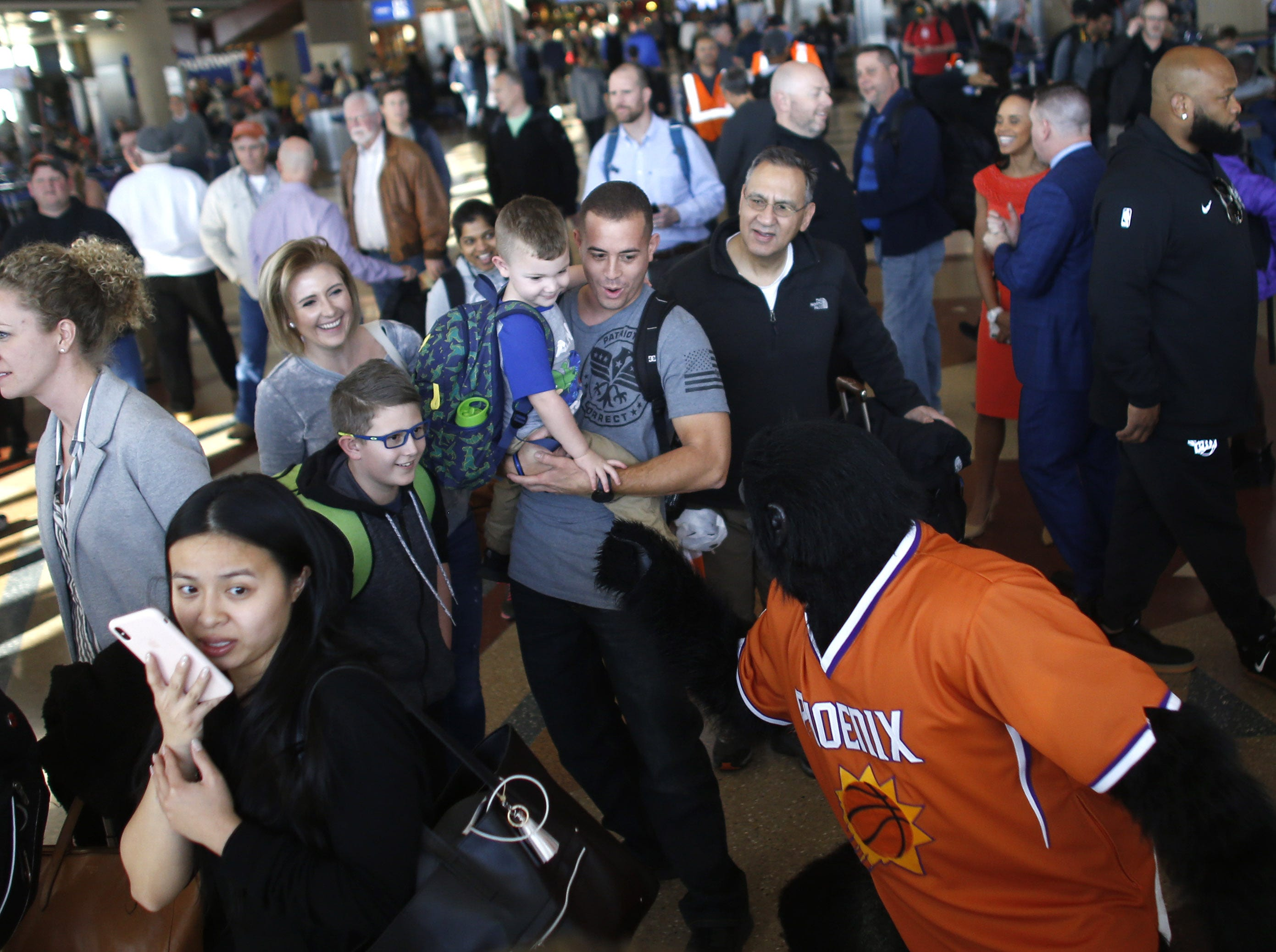 "Suns Gorilla high-fives young fans during a Suns and Southwest ""trading places"" event where players took on the roles of Southwest Airlines employees at Phoenix Sky Harbor Airport in Phoenix, Ariz. on February 7, 2019."