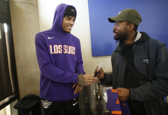 "Suns' Kelly Oubre signs a jersey of a fan during a Suns and Southwest ""trading places"" event where players took on the roles of Southwest Airlines employees at Phoenix Sky Harbor Airport in Phoenix, Ariz. on February 7, 2019."