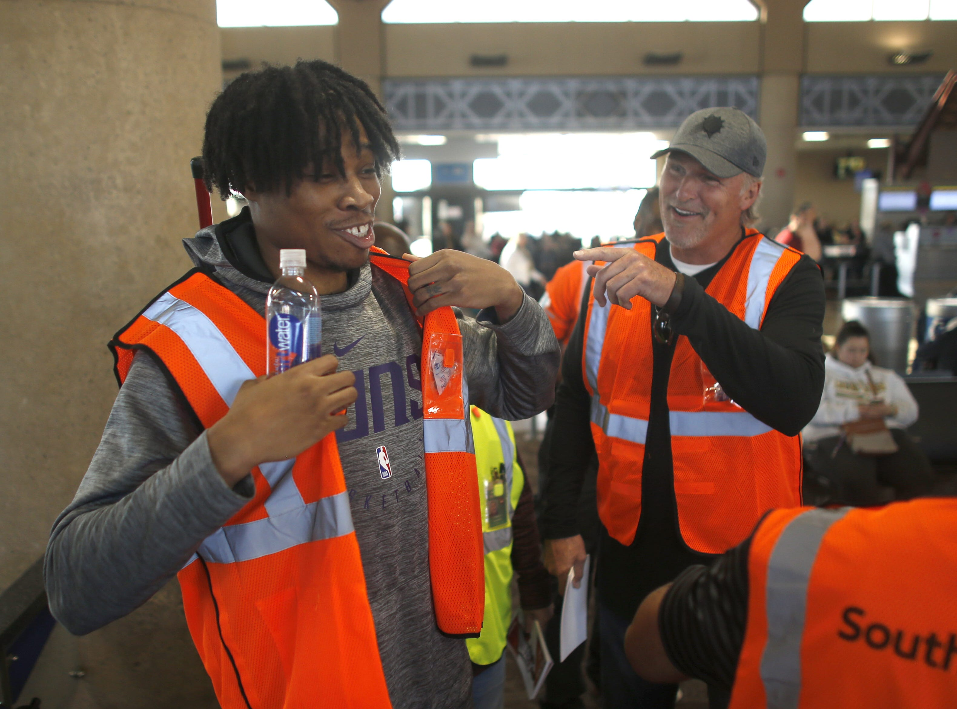 "Suns' Richaun Holmes (L) laughs with Tom Chambers (R) as they prepare to take to the tarmac during a Suns and Southwest ""trading places"" event where players took on the roles of Southwest Airlines employees at Phoenix Sky Harbor Airport in Phoenix, Ariz. on February 7, 2019."