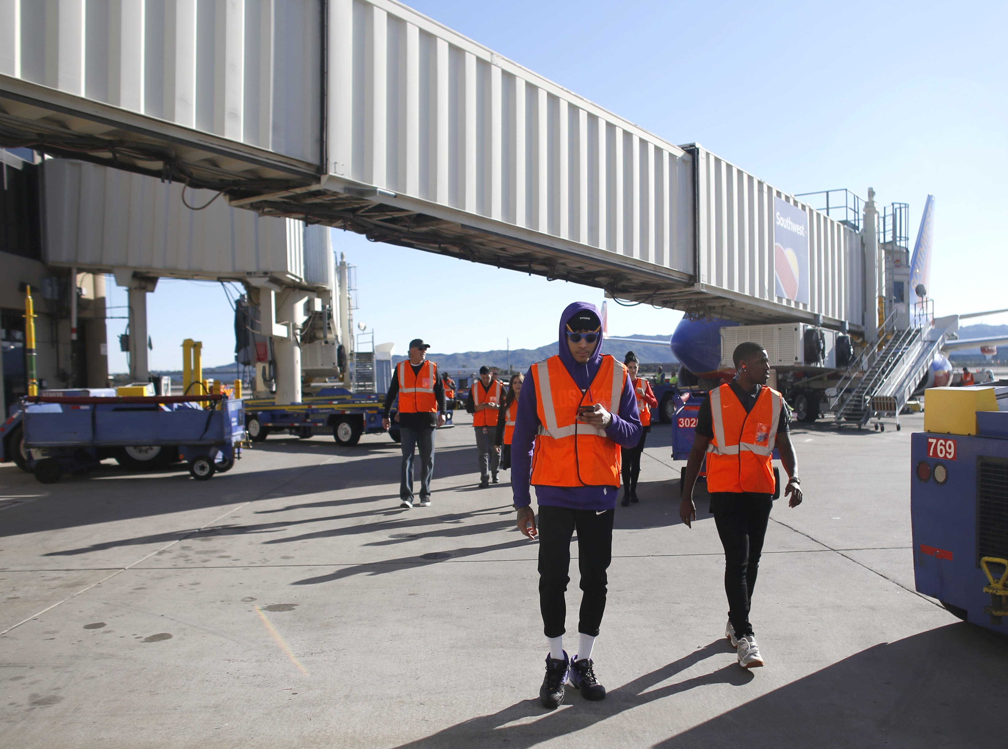 "Suns' Kelly Oubre and Jawun Evans make their way on the tarmac during a Suns and Southwest ""trading places"" event where players took on the roles of Southwest Airlines employees at Phoenix Sky Harbor Airport in Phoenix, Ariz. on February 7, 2019."
