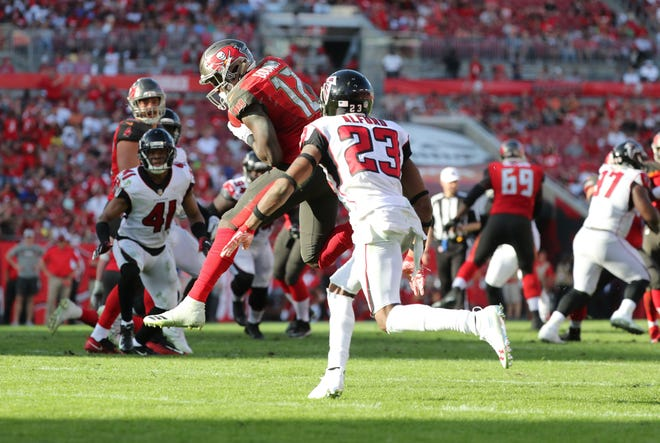 Dec 30, 2018; Tampa, FL, USA; Tampa Bay Buccaneers wide receiver Chris Godwin (12) catches the ball over Atlanta Falcons cornerback Robert Alford (23) and runs it in for a touchdown during the second half at Raymond James Stadium. Mandatory Credit: Kim Klement-USA TODAY Sports