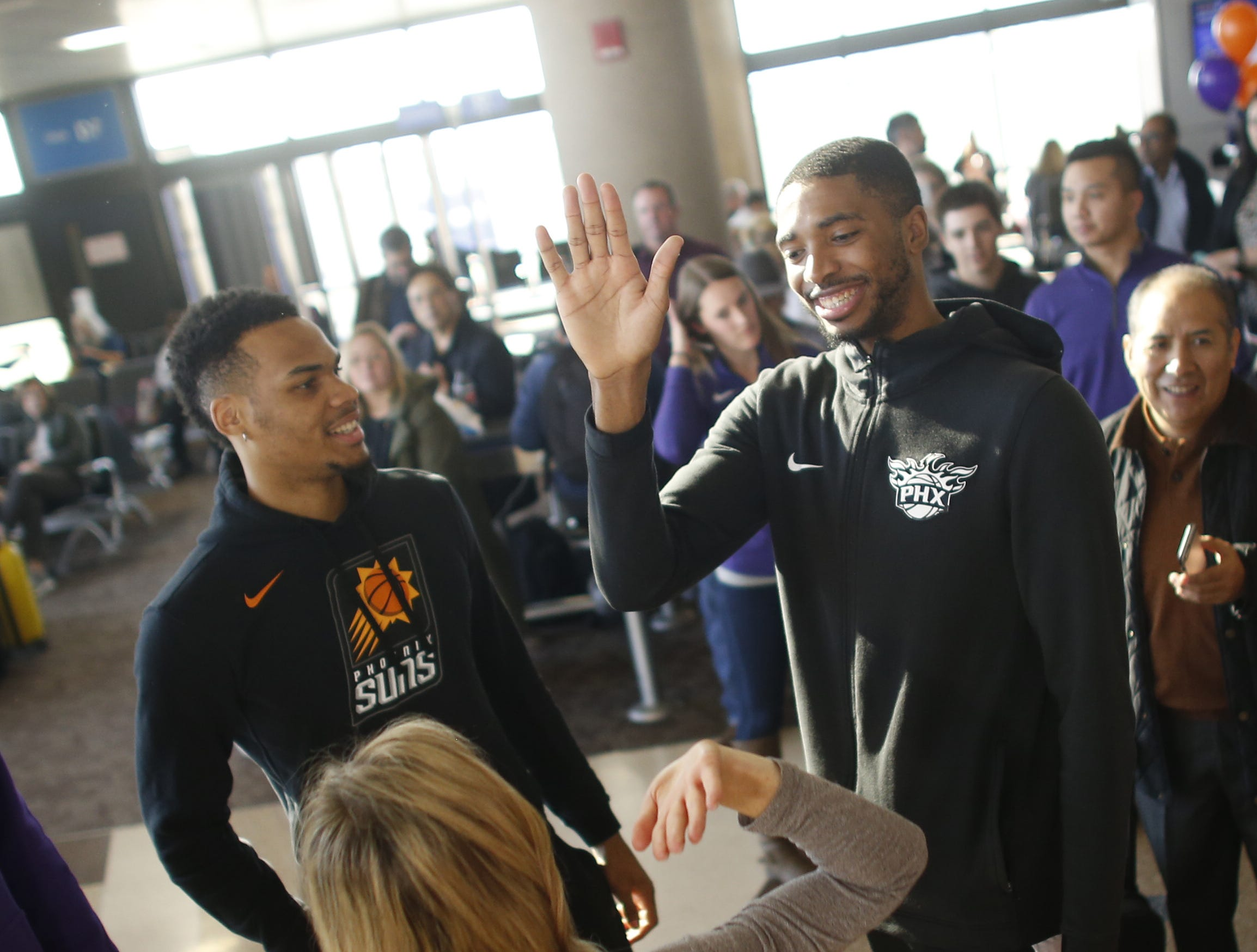 "Suns' Mikal Bridges high-fives a fan during a Suns and Southwest ""trading places"" event where players took on the roles of Southwest Airlines employees at Phoenix Sky Harbor Airport in Phoenix, Ariz. on February 7, 2019."