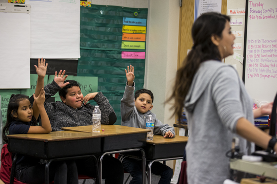 Third grade students raise their hands in Erica Kurz's class on Thursday, Feb. 7, 2019, at Longfellow Elementary in Mesa, Ariz.