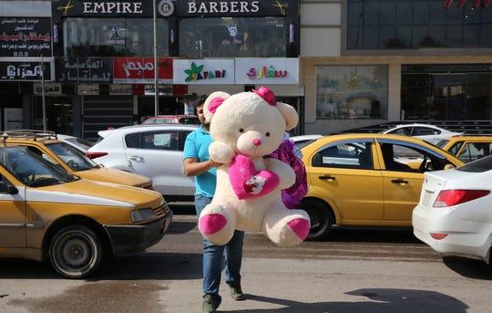 Un hombre carga un gran oso de peluche por la calle.