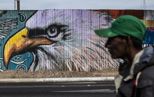 Un hombre perteneciente a la caravana migrante camina frente al cerco fronterizo, donde se observa un mural de un águila.
