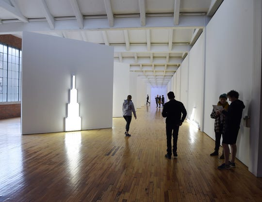 Visitors explore an art installation by artist Dan Flavin at Dia:Beacon.