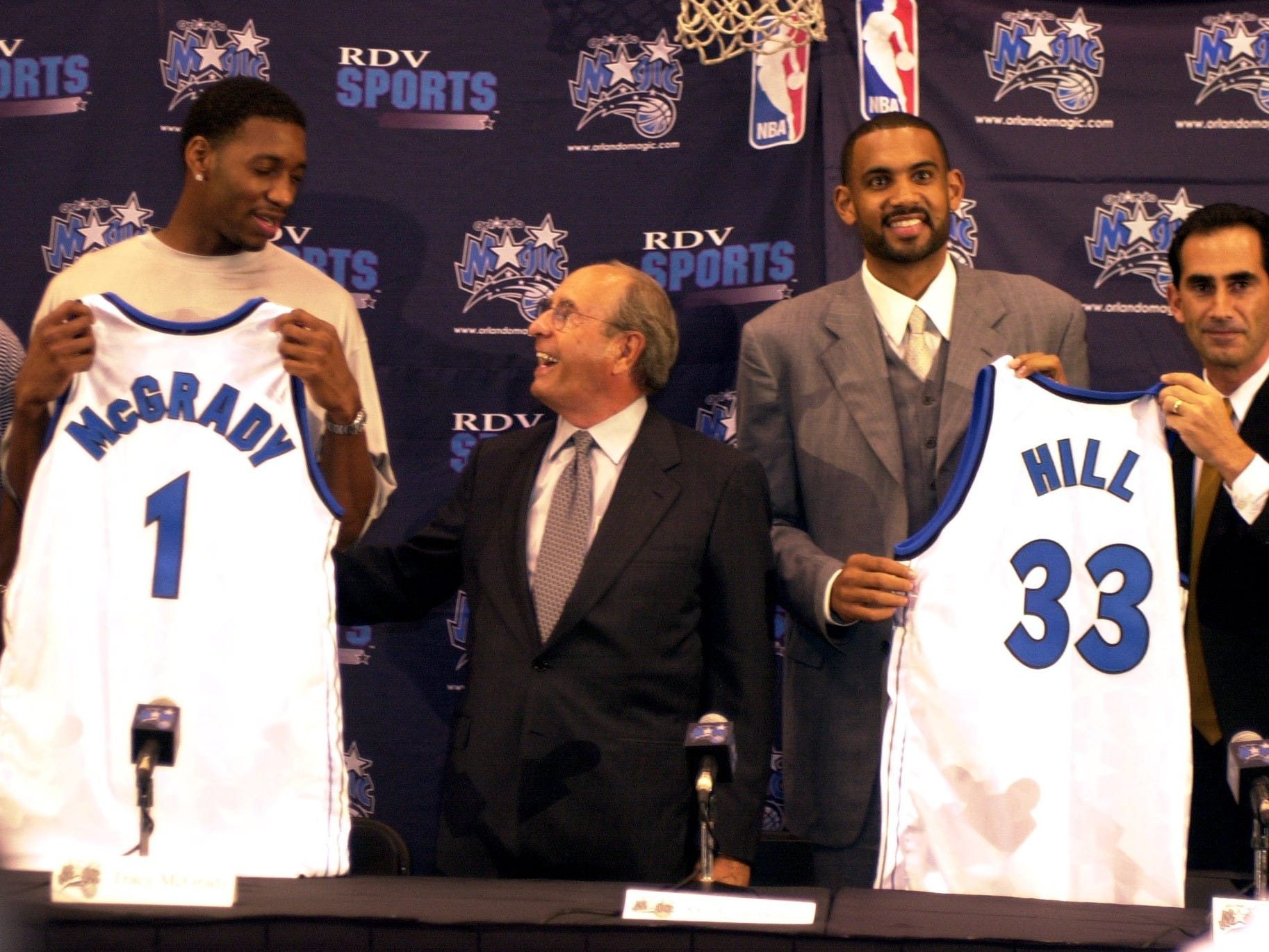 NBA stars Tracy McGrady, second from left, and Grant Hill, second from right, proudly display their new jerseys as the Orlando Magic celebrated their signings in a news conference in 1999. Standing with the new players are: Magic coach Doc Rivers, far left, owner Rich DeVos, center, and general manager John Gabriel, far right.
