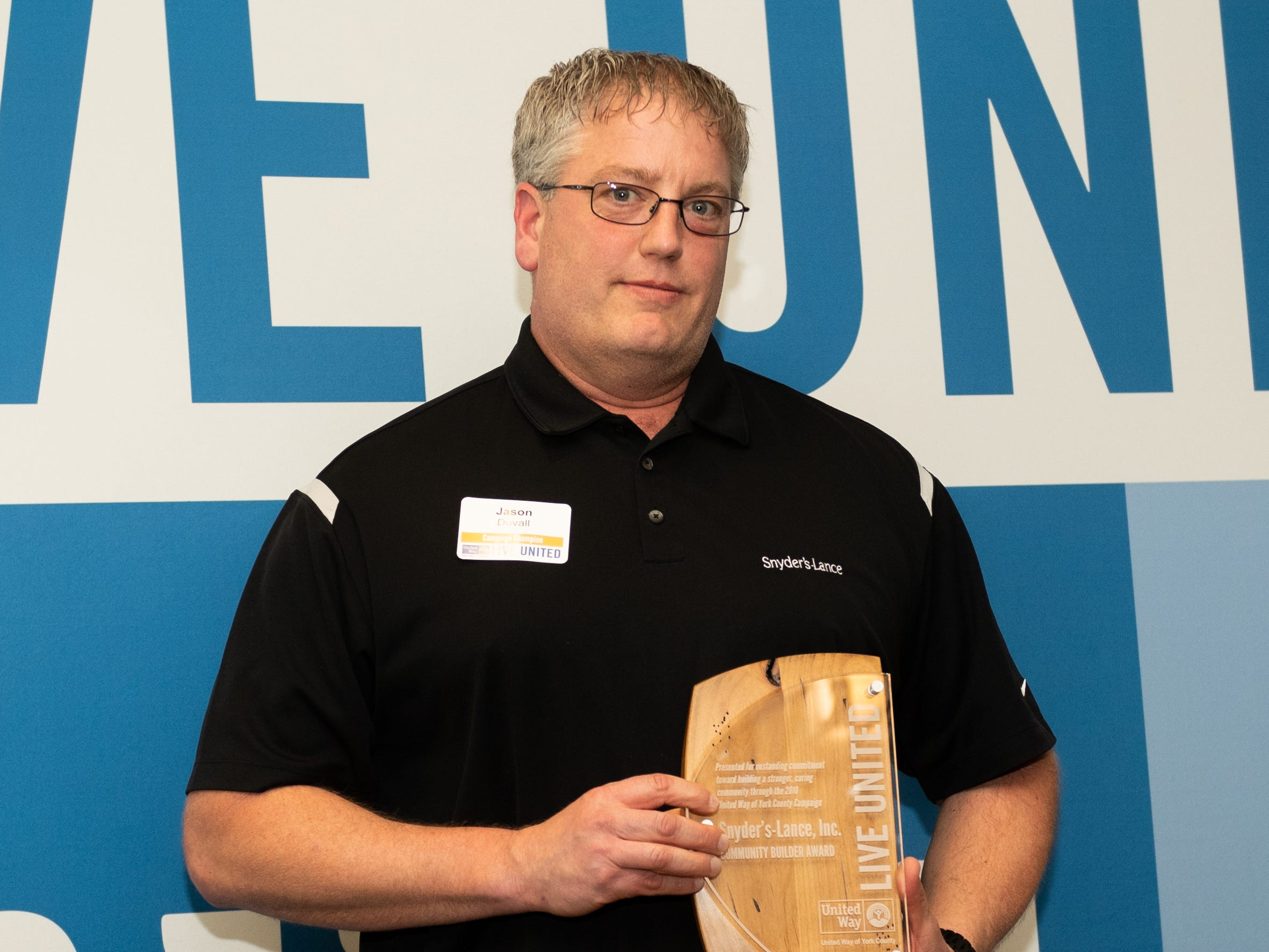 A Representative of Snyder's-Lance, Inc. poses with a Community Builder Award during the 2018 United Way Campaign Celebration, February 7, 2019.