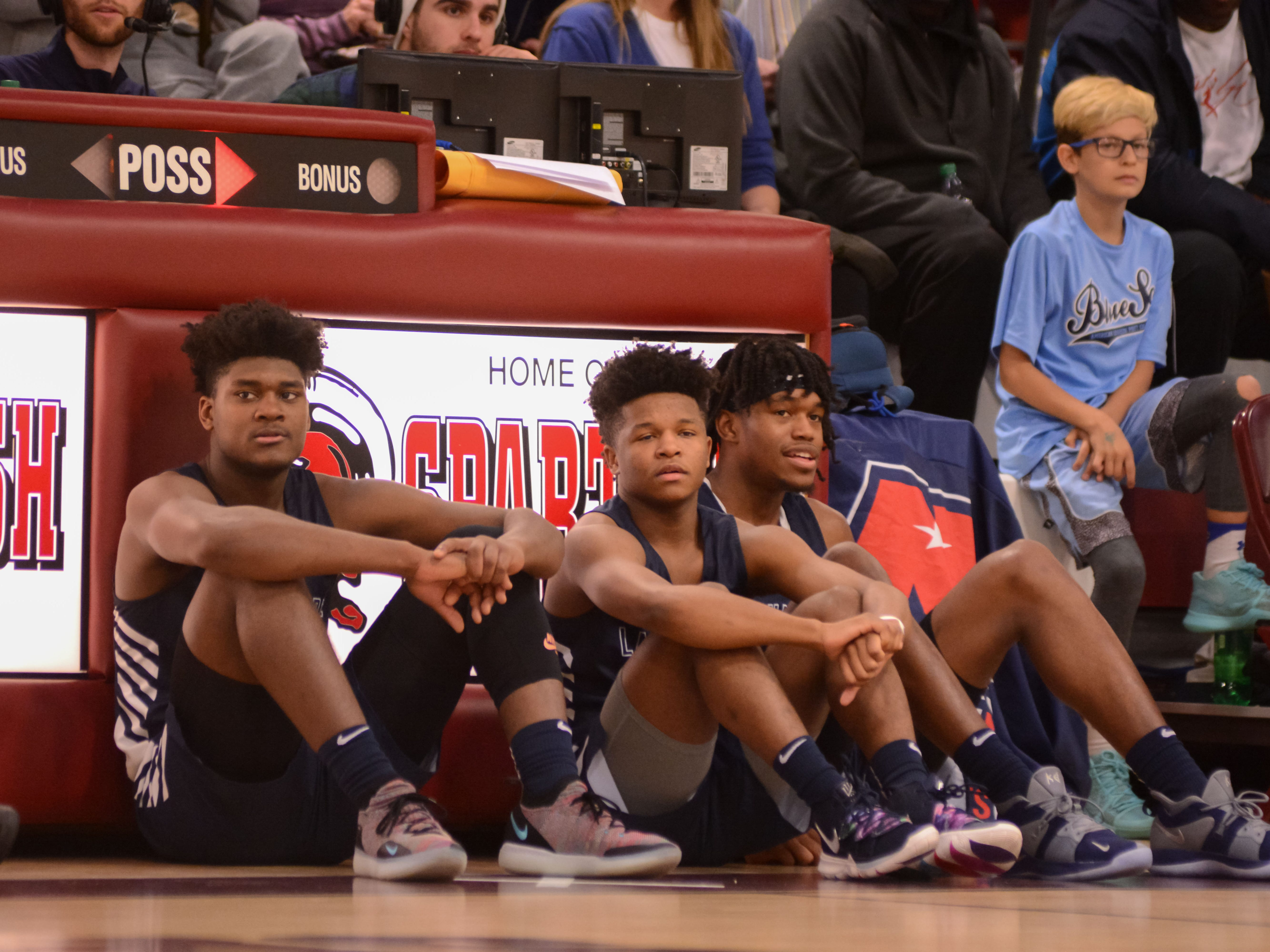 Former Irondequoit star Gerald Drumgoole, left, sits near the scorer's table as he waits to check into a game for the La Lumiere School at the Bob Kirk Invitational Tournament in Cumberland, Maryland.