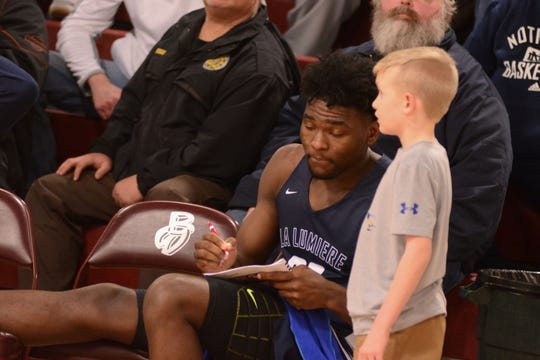 Former McQuaid star Isaiah Stewart signs an autograph for a young fan as he ices his ankle during a game at the Bob Kirk Invitational in Cumberland, Maryland. Stewart, who is ranked among the top 10 high school players in the country, plays for top-ranked La Lumiere of La Porte, Indiana.
