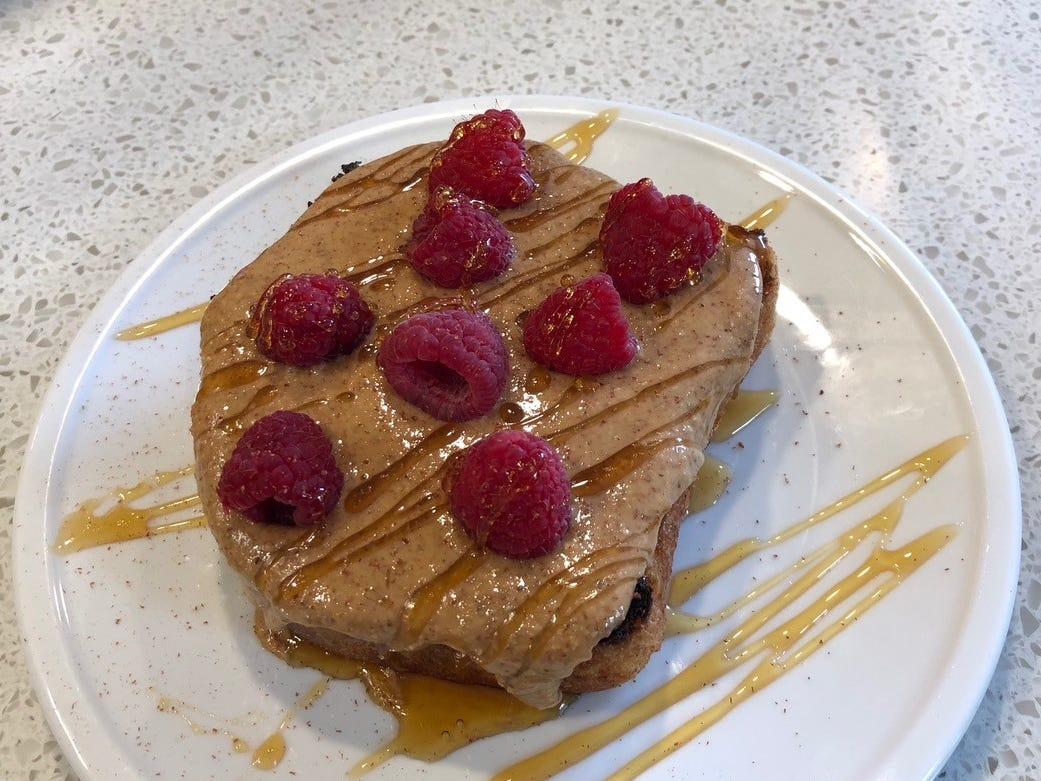 Sourdough toast with almond butter, honey, cinnamon and raspberries at the Coffee Bar.
