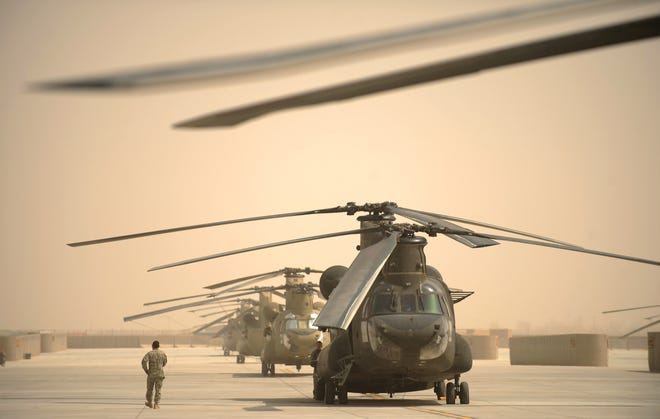 A US airman walks past a row of Chinook helicopters at Kandahar airbase in southern Afghanistan in 2011.