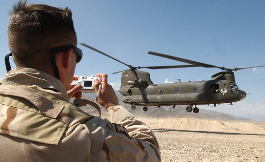 A U.S. soldier gets photos of U.S.  CH-47 Chinook helicopter as it takes off from the Laghman PTR's air field in Laghman province, east of Kabul, Afghanistan in 2005.