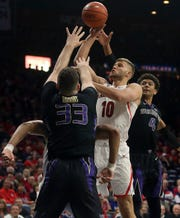 Arizona forward Ryan Luther (10) jumps for the basket while defended by Washington forward Sam Timmins (33) and guard Matisse Thybulle (4) in the first half of an NCAA college basketball game in Tucson, Ariz., Thursday, Feb. 7, 2019.