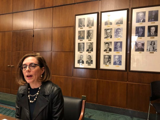 Oregon Gov. Kate Brown speaks to reporters in front of pictures of previous state governors in Salem, Ore., Thursday, Feb. 7, 2019.  Gov. Brown weighed in on the political crisis in Virginia, saying her counterpart there should step down and that the problem of whites going in blackface is due in part to a lack of awareness and stupidity.