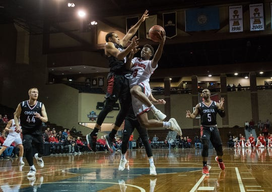 Omaha's JT Gibson (0) tries to block USD's Triston Simpson (3) from making a shot during a game at the Sanford Pentagon in Sioux Falls, S.D., Thursday, Feb. 7, 2019.