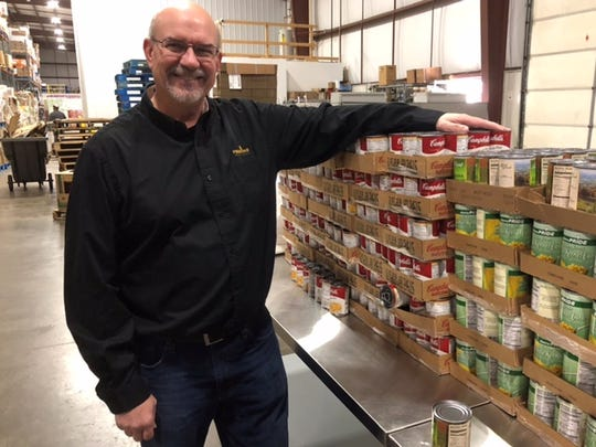 George Rokusek, western operations manager for Feeding South Dakota, stands among food products that will be placed into bags that fit into backpacks of needy children. Rokusek said the backpack program foods are chosen specifically so children of working parents can easily prepare and consume them without adult assistance.