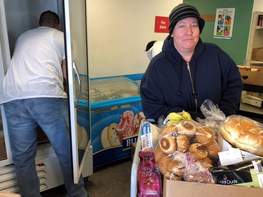 Lisa Henley of Summerset, S.D., received a cart full of food from the Feeding South Dakota pantry in Rapid City recently. Henley, 39, is a mother of two who enrolled in the food stamp program after she broke her wrist and lost her job as a waitress.