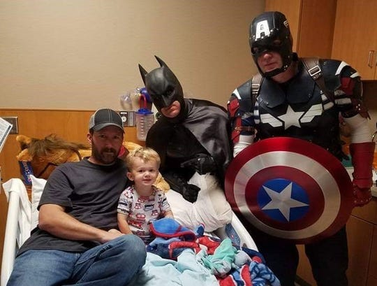 Terry Mattke, dressed as Batman, joins Captain America in a recent hospital trip to visit with sick children and their families.