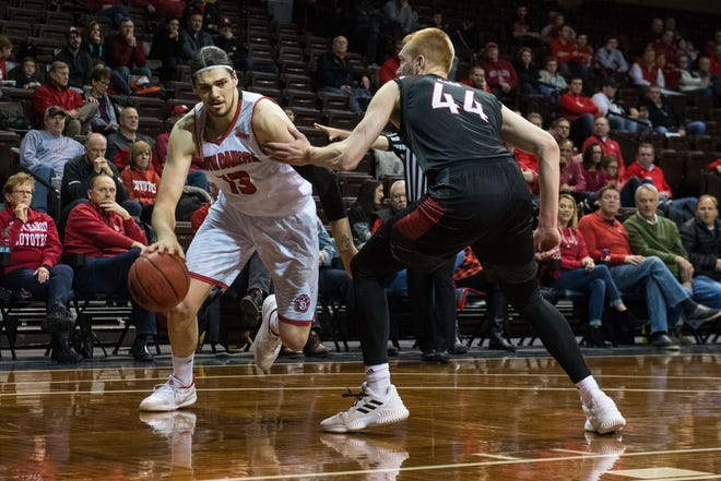USD's Matt Johns dribbles the ball past Omaha's Mitch Hahn (44) during a game at the Sanford Pentagon in Sioux Falls, S.D., Thursday, Feb. 7, 2019.