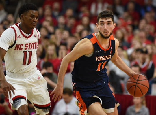 Virginia Cavaliers guard Ty Jerome (11) dribbles the ball as North Carolina State Wolfpack guard Markell Johnson (11) defends during the second half at PNC Arena.