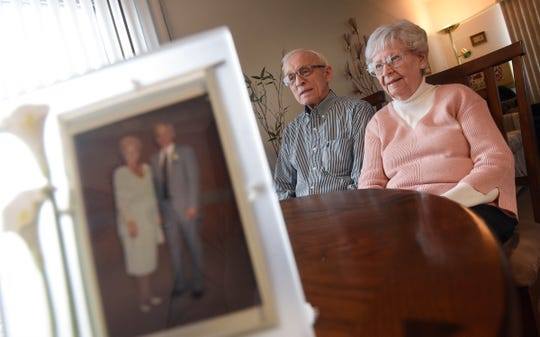 Marcel Tadych and Doree Canfield talk about their marriage behind their wedding photo during an interview Thursday, Feb. 7, at their home in Sartell.