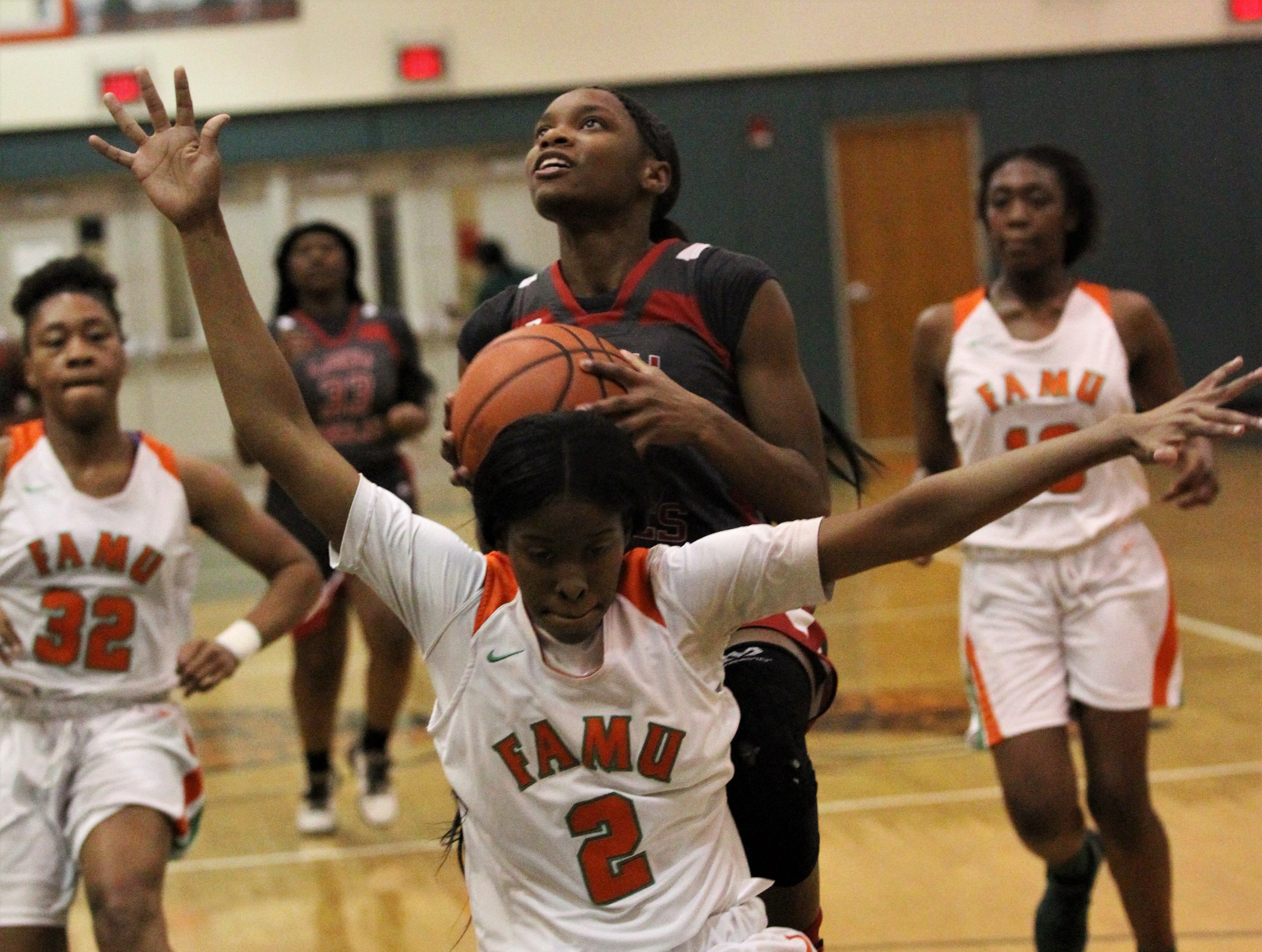 NFC junior Alexsis Thomas goes up for a layup on the back of FAMU DRS senior Diamond Douglass as FAMU DRS' girls basketball team beat NFC 59-41 for a District 1-3A title on Jan. 7, 2019.