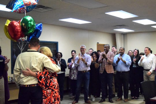 Jeremy (far left) and Holly Shaw hug after he is surprised with the 2018-19 LCS School Related Employee of the Year Award.