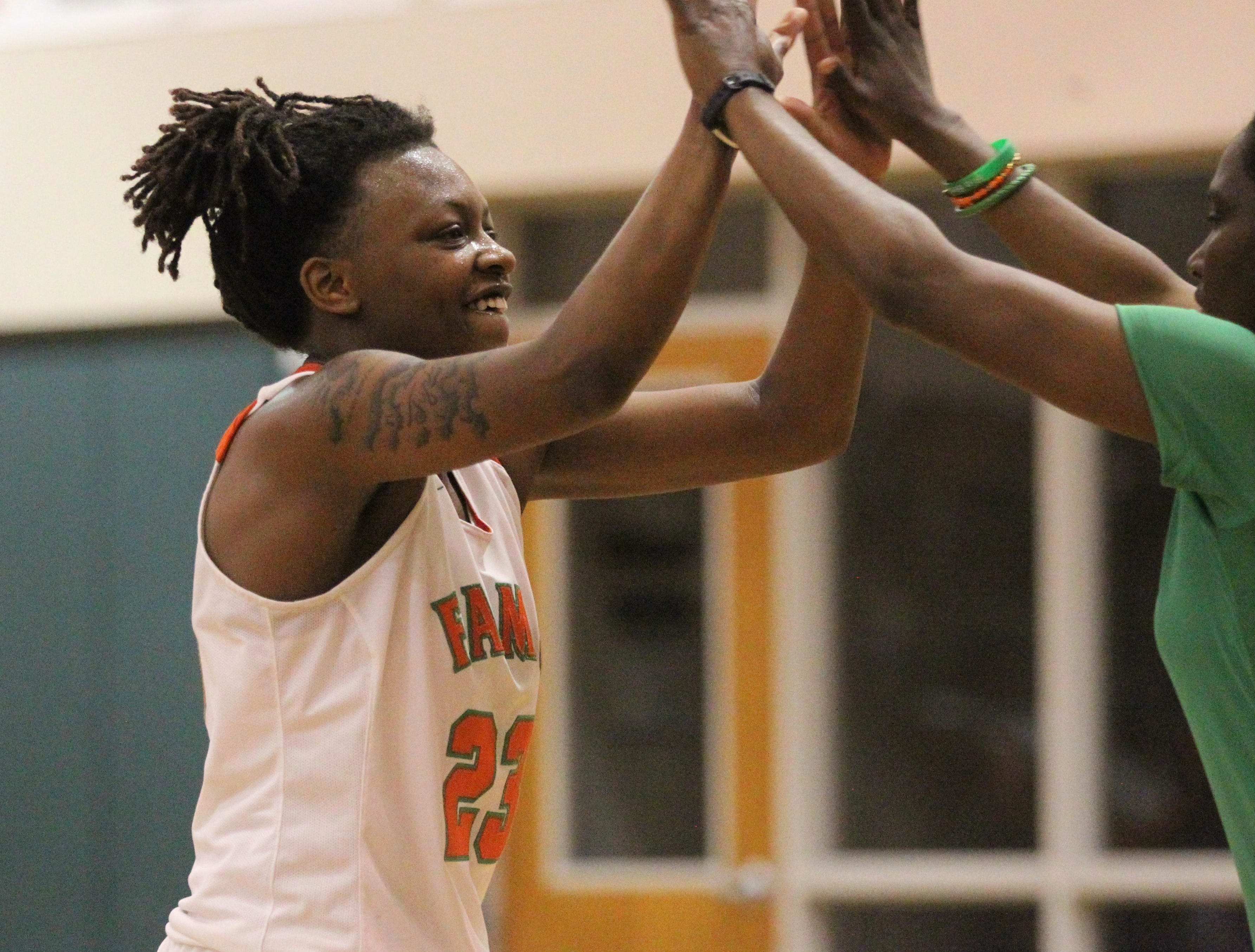 FAMU DRS senior Ayleshia Vickers high fives her coach as FAMU DRS' girls basketball team beat NFC 59-41 for a District 1-3A title on Jan. 7, 2019.