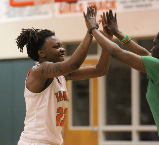 FAMU DRS senior Aylesia Vickers high fives her coach as FAMU DRS' girls basketball team beat NFC 59-41 for a District 1-3A title on Jan. 7, 2019.