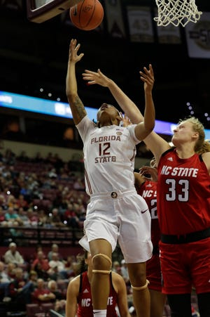 Florida State Seminoles guard Nicki Ekhomu (12) drives in a layup with North Carolina State Wolfpack center Elissa Cunane (33) reaching from behind trying to block the shot. The Florida State Seminoles host the NC State Wolfpack at the Tucker Civic Center, Thursday Feb. 7, 2019.
