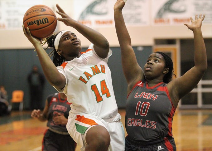 FAMU DRS freshman Ameari Logan hangs in the air for a layup past NFC's Eva Holmes as FAMU DRS' girls basketball team beat NFC 59-41 for a District 1-3A title on Jan. 7, 2019.