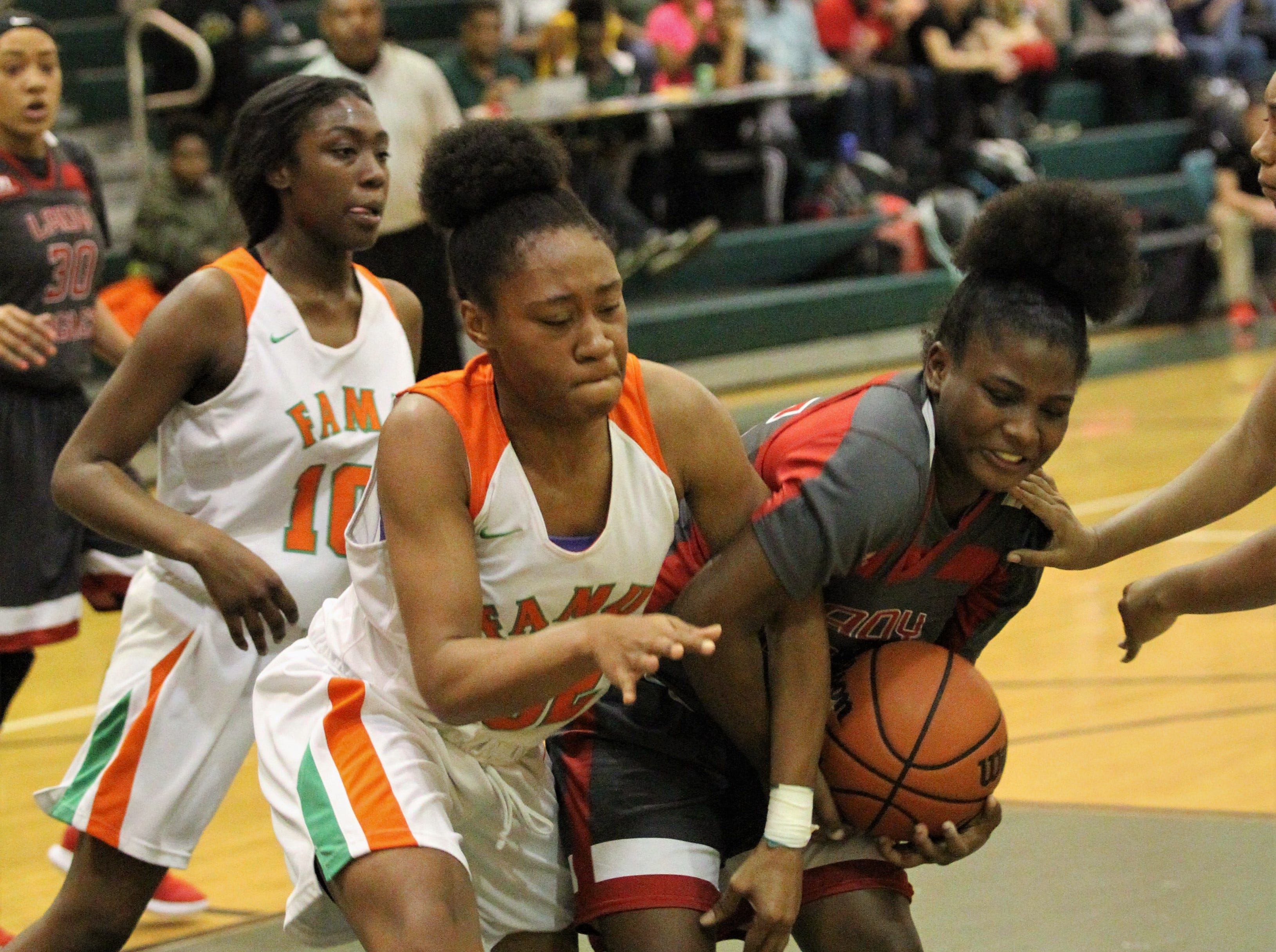 NFC freshman Alexis Howard gets tangled up with FAMU DRS sophomore Kennyhia Patterson after a rebound as FAMU DRS' girls basketball team beat NFC 59-41 for a District 1-3A title on Jan. 7, 2019.
