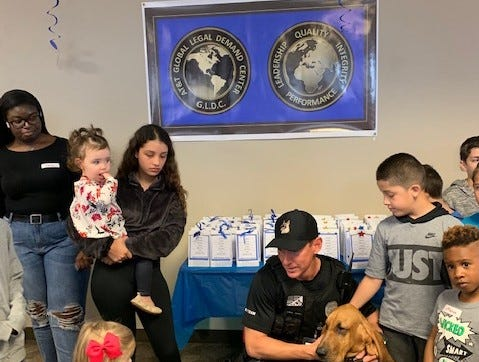 Jupiter Police K9 Officer Chad Norman kneels with K9 Bandit as Dawson Faulkner, foreground, decides to pet the police dog. Also pictured are, from left, Laila Likely, Angelina Sanchez with Ella Grace Schriver, Christian Sanchez Jr. and Mason Owen.