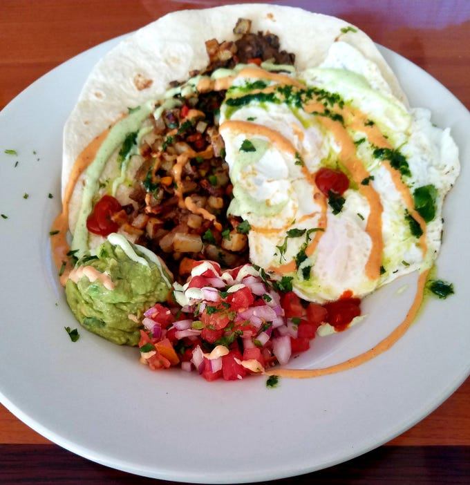 Three Little Birds Cafe's huevos rancheros consisted of a grilled flour tortillas topped with refried black beans, diced potatoes and pepper mix, avocado smash, pico de gallo, chimichurri and garnished with chipotle and cilantro sauces.
