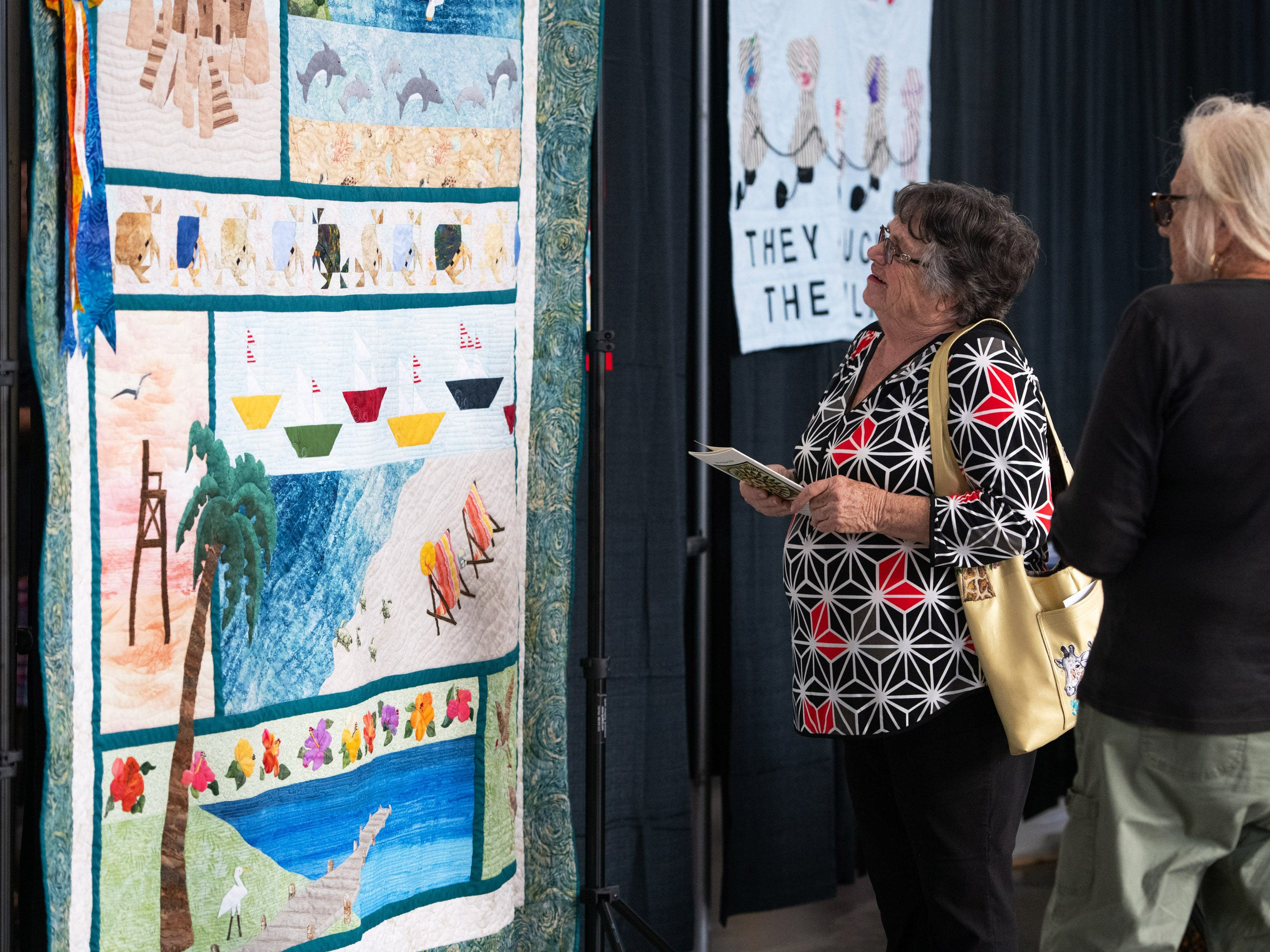"Betty Hamer (left) and her friend Caryl Hunt, both of Sebastian, take a closer look at the Vero Beach Centennial Quilt named ""A Day at the Beach"" at the 40th annual Sunbonnet Sue Quilter's Guild Show at the Indian River County Fairgrounds on Friday, Feb. 8, 2019, in Vero Beach. ""There's a lot of time put into this one,"" said Hamer of the quilt, adding, ""It's just splendid."" The show continues 10 a.m. to 4 p.m. Saturday."