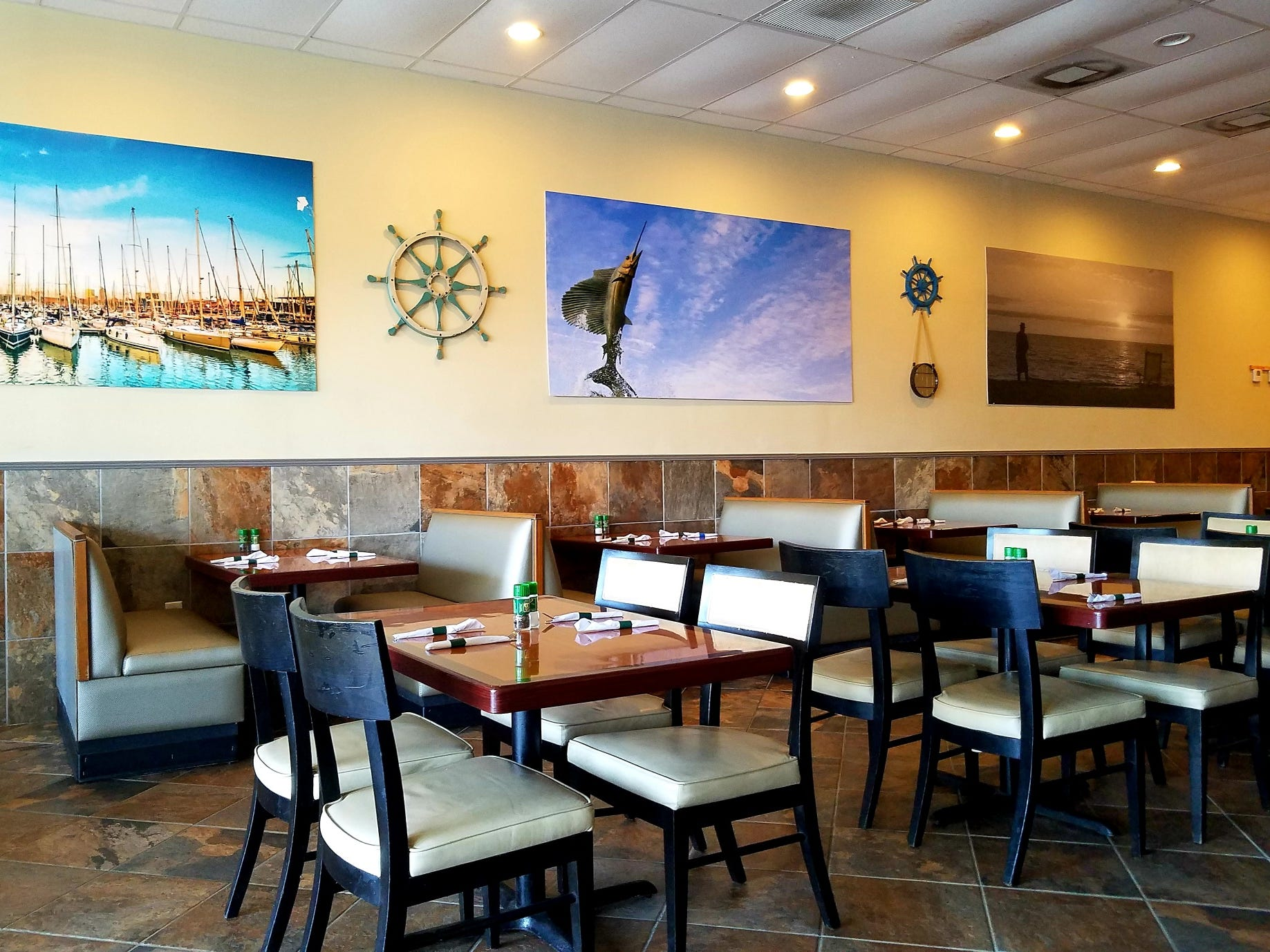 The interior of Three Little Birds Cafe  provides customers with new booths and tables, in a bright and clean atmosphere.
