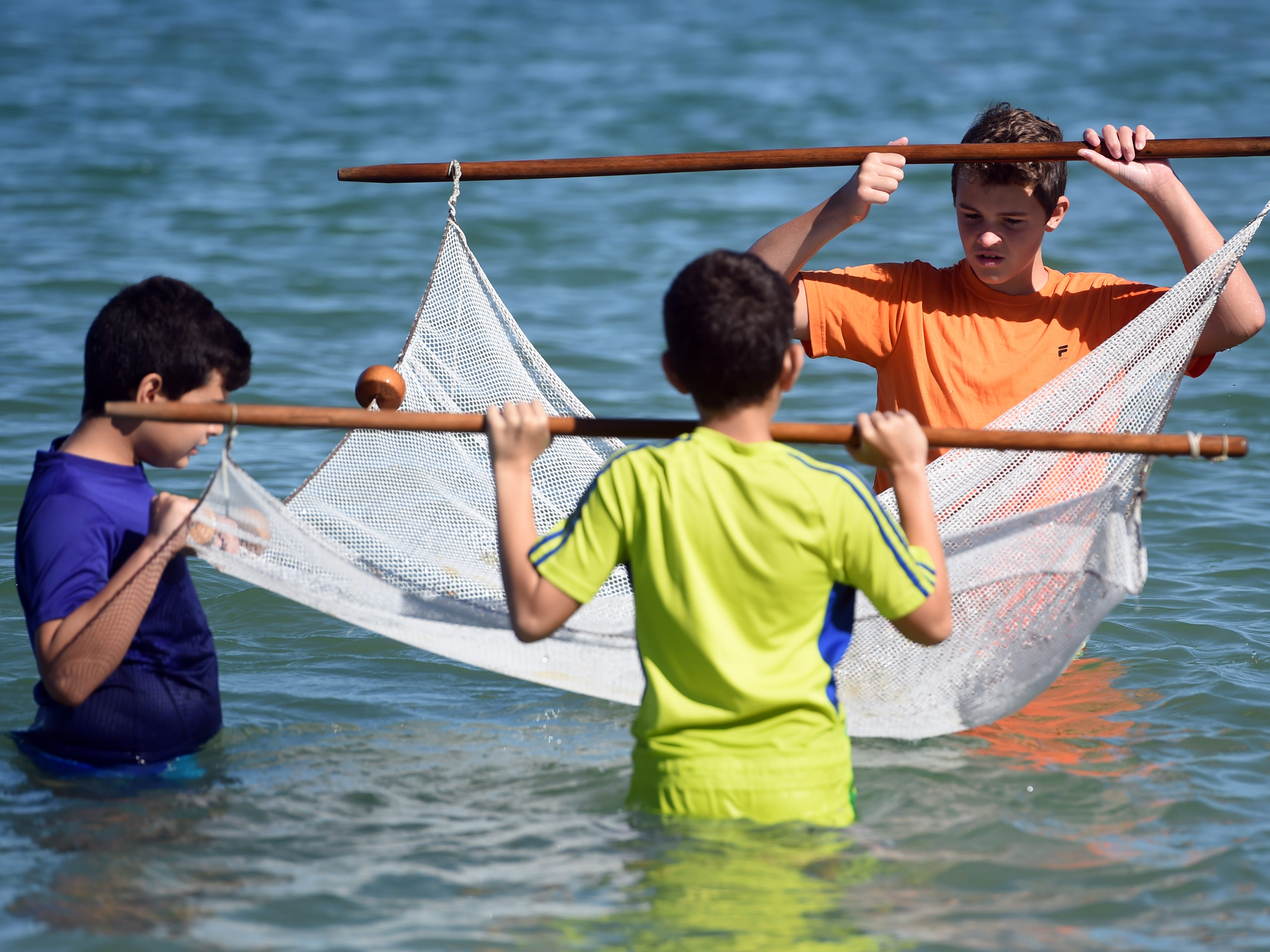 Homeschool students Alex (from left), 11, and Victor Borges, 14, and Ethan Degoede, 13, seine for plant and animal life in the Indian River Lagoon near the Fort Pierce Inlet on Friday, Feb. 8, 2019 during a Homeschool Hopper biodiversity program at the St. Lucie County Aquarium. The boys, along with 14 other students, studied two sites on the lagoon comparing the biodiversity and health of each site.