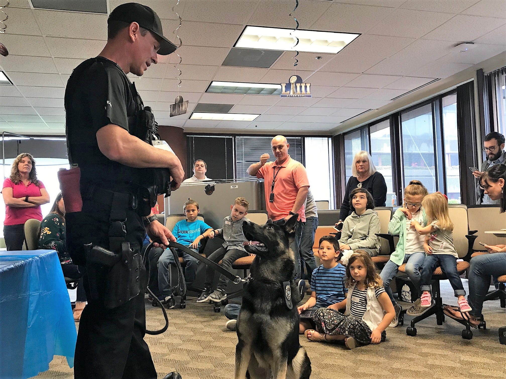 Employees and children at AT&T's Global Legal Demand Center in North Palm Beach watch as Jupiter Police K9 Officer Chad Norman instructs K9 Corby during a demonstration on Take Your Child to Work Day.